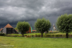 Summer storm in Dutch village (Monika Kalczuga) Tags: storm holland building nature netherlands architecture clouds landscape outdoor windmills molen zaanseschans stormclouds typicaldutch dutcharchitecture
