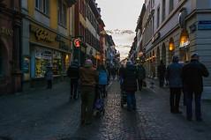Walking first of January (Alexander Pugatschewski) Tags: lighting street city winter people germany advertising cityscape dusk january illumination newyear heidelberg storefronts streetphotos
