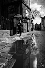 City Reflections (nigelhunter) Tags: street old city sky urban man reflection building bus tree water lines yellow clouds puddle pavement candid stop lancaster