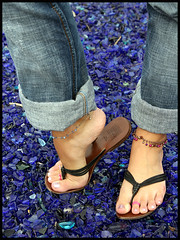 Tia's feet in flip flops (sunnystreets) Tags: street city feet female outdoors foot shoes toes arch sandals polish jewellery jeans rings nails flip flops pedicure anklets