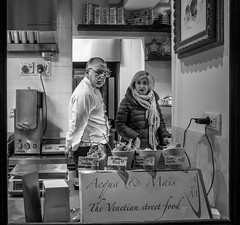 Hungry? (onetwothreepic) Tags: street venice food woman white man black photography restaurant couple eating cook streetphotography