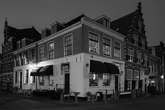 Dutch Corner (McQuaide Photography) Tags: street old city longexposure nightphotography winter light urban blackandwhite bw house holland building haarlem netherlands monochrome dutch architecture night zeiss corner photoshop outside mono restaurant licht blackwhite lowlight streetlight europe oldstyle nacht outdoor availablelight sony traditional tripod nederland wideangle illuminated nesta fullframe alpha huis residential oud stad authentic manfrotto noordholland gebouw lightroom huizen straat horeca hoek canalhouse wideanglelens 1635mm northholland a7ii grachtenpand groothoek bakenessergracht variotessar mirrorless sonyzeiss donkerespaarne mcquaidephotography ilce7m2 nestahaarlem