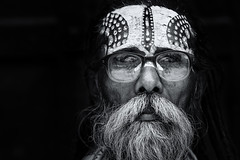 Sadhu Series, Two (Axel Halbgebauer) Tags: street travel nepal portrait people blackandwhite bw india monochrome face closeup blackbackground zeiss dark beard prime glasses indian sony religion streetphotography highcontrast hindu hinduism sadhu holyman southasia sonyalpha streetportait sonnar13518za sonya7r2