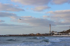 A plane on it's approach to Sde Dov Airport and surfers paddling out just before sunset (jonafin1970) Tags: plane israel telaviv middleeast surfers
