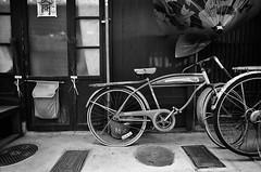 Punctured (Purple Field) Tags: street new bw film monochrome bicycle japan facade analog zeiss umbrella 35mm walking alley kyoto fuji iso400 g year rangefinder contax carl   g2 neopan  f28    21mm presto  biogon              stphotographia