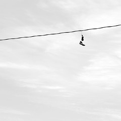 Chucks on a Wire (ScottNorrisPhoto) Tags: urban blackandwhite usa wisconsin photography wire shoes moody outdoor pair overcast minimal sneakers explore converse milwaukee hanging powerline tied stark simple chucks minimalist squarecrop allstars chucktaylor shoestring 365project scottnorrisphotography