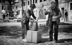 Quick, find some money to pay the trolley man. (Just Ard) Tags: street people blackandwhite bw woman white black blancoynegro monochrome face bag square person photography 50mm mono nikon noiretblanc zwartwit box trolley candid d750 unposed murano  biancoenero searching schwarzundweis justard