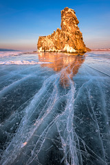 Famous Baikal Lake Ice and Island Ogoy at Sunset, Baikal Lake, Russia (ansharphoto) Tags: travel blue winter light sunset vacation sky cliff white mountain lake snow cold texture tourism ice nature water rock landscape island evening march frozen spring europe frost break view russia outdoor stones peak landmark surface glacier siberia sacred environment transparent cracks icy siberian icicles baikal glacial shamanism olkhon ogoy ogoi