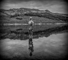 Man of Steel (cheese and pickle) Tags: sky blackandwhite sculpture lake mountains reflection water reflections landscape mono scotland britain outdoor scenic mountainside scottishhighlands