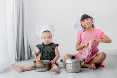 Asian children playing  chef at home. (Nuiiko) Tags: people food white house playing cute home cooking kitchen girl hat childhood recipe asian fun person japanese kid healthy child hand little sister eating interior small joy gray chinese paddle cook adorable lifestyle korean homemade human together chef thai meal pan ideas job enjoyment preparation creep preparing concepts ingredient occupation