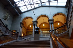 Empty Spaces (KevinIrvineChi) Tags: light sculpture white chicago black paris art museum architecture bronze stairs amber cool warm pattern arch afternoon open cathedral space empty patterns board sony columns skylight rail grand arches ceiling institute chandelier staircase handrail 1910 marble railing atrium edu artic polished spaces sweeping lateafternoon womans emptyspaces flickrfriday fondeur c1906 18611944 rudier dscrx100 enchainedaction aristidejosephbonaventuremaillolfrench