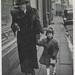 Woman and child walking down a sidewalk