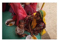 a handful of rice (handheld-films) Tags: travel portrait people food woman india girl festival rural children lunch women child rice eating indian mother documentary portraiture rajasthan mela harvesttime subcontinent rurallife