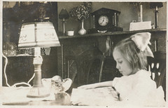 Little girl reading at a table (simpleinsomnia) Tags: old white black lamp girl monochrome vintage found reading book blackwhite little antique interior snapshot photograph littlegirl vernacular foundphotograph