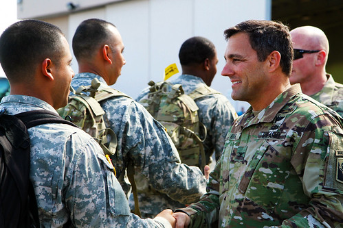 Col. John Haas, commander, 53rd Infantry Brigade Combat Team, shakes hands with Soliders of the 1st Battalion, 124th Infantry Regiment as they board buses following a departure ceremony at an aircraft hangar in Fort Lauderdale, Fla., April 10. Joined with