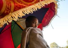 Kid holding an umbrella during an orthodox celebration in Lalibela, Ethiopia (Eric Lafforgue) Tags: africa umbrella child ethiopia lalibela ethio161496