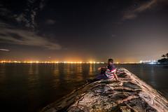 Unperturbed (arnabjosephite) Tags: ocean blue light sea sky people reflection beach yellow clouds port stars sand singapore ships