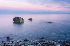 Blue hour romance (Nick Panagou) Tags: longexposure blue light sunset red sea sky seascape motion mountains reflection beach nature water rock clouds contrast landscape rocks exposure colours purple outdoor greece bluehour cloudysky thessaly flickrsbest magnesia canon400d flickrbest