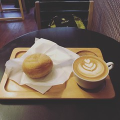 """""""さくら""""ドーナツとカフェラテ。代々木上原のお気に入りドーナツ屋ハリッツです。さくらは桜風味のパウダーがかかったあんドーナツ。ハリッツのもっちりしたドーナツにぴったり。定番のスイート65はお持ち帰りです。 #カフェ #cafe #ドーナツ #ハリッツ #代々木上原"""