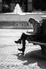 Shadows, revision and a waterfountain (Yannis_K) Tags: blackandwhite woman monochrome reading shadows cobblestone study waterfountain revision 85mmf18g nikond7100 nikon85mmf18g yannisk