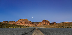 red rock moonrise (almostsummersky) Tags: redrockcanyon road morning travel sky moon mountains turn sunrise us spring highway sandstone rocks unitedstates desert bend lasvegas horizon nevada hill canyon cliffs line lane curve reflector nationalconservationarea aztecsandstone