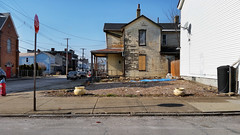 Two urns on a vacant lot, Larimer, February 28, 2016 (real00) Tags: corner deadpan debris decay dirt fence house intersection landscape larimer manalteredlandscape neighborhood peelingpaint pittsburgh porch quirky rubble rustbelt sad sidewalk tarp urban urbanlandscape