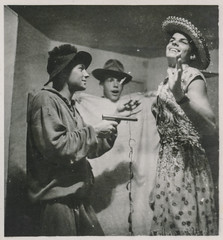 Young man holds a toy gun on another man wearing a woman's dress (simpleinsomnia) Tags: old gay white man black monochrome vintage found blackwhite costume gun cross antique snapshot young crossdressing dressing photograph vernacular interest youngman foundphotograph embracing gayinterest