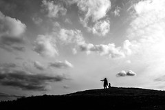 Over There! (Warfield360) Tags: woman girl contrast hair mom shadows child wind hill silhouettes urbannature gesture breeze pointing darkclouds citypark heritagepark