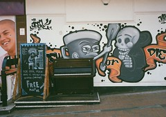 op - oasis piano (johnnytakespictures) Tags: street music art film coffee pen graffiti wooden lomo lomography birmingham play tea piano olympus musical oasis instrument analogue halfframe ee3 asone lomographycn400