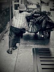 Heavy Burden - Bangkok (jcbkk1956) Tags: street blackandwhite woman thailand mono nikon bangkok grill thai coolpix bags cart heavy burden pushing sukhumvit thonglo viagginelmondo worldtrekker