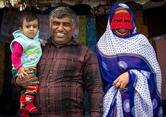 a bandari woman with her husband and son wearing a traditional mask at panjshambe bazar, Hormozgan, Minab, Iran (Eric Lafforgue) Tags: boy red portrait people woman face childhood horizontal outdoors persian kid clothing asia child veil dress mask iran market muslim islam traditional father religion mother hijab culture persia hidden identity human covered iranian bazaar adults islamic burqa customs middleeastern sunni 3people burka chador 30sadult threepeople balouch hormozgan lookingatcamera burqua  bandari  embroidering  iro thursdaymarket  minab colourpicture  borqe panjshambe boregheh iran034i2736