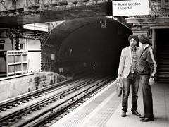 Singh Along (Douguerreotype) Tags: city uk 2 two england people urban blackandwhite bw london monochrome sign train mono britain candid tracks tunnel rails gb british conversation whitechapel