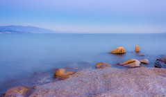 Dreaming (Nick Panagou) Tags: longexposure blue light sunset sea seascape mountains nature water rock clouds contrast canon landscape twilight rocks exposure colours outdoor minimal greece waterscape flickrsbest magnesia canon400d flickrbest coudysky canonefs1855mmf3556isii