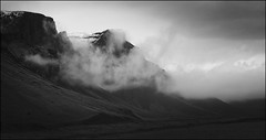 Clouds Rising Pano -BW (Firery Broome) Tags: travel sunset blackandwhite bw panorama snow mountains nature monochrome clouds photoshop landscape blackwhite iceland europe rocky olympus valley 365 cloudporn worldtravel mountaintops naturelovers earthnature lateautumn alienskin blackandwhitelandscape blackandwhitenature viveza cloudsrising exposurex sliderssunday olympusem10 europe2014