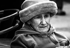 Portrait R22 (pootlepod) Tags: street old winter portrait blackandwhite senior coffee monochrome face hat sex closeup lady female mouth fur photography eyes warm alone sitting chairs tea drink pavement candid profile drinking warmth wrapped lips sidewalk coastal devon mature elderly seats zen heat lonely citizen wrinkles cosy stmarychurch canon60d stphotographia nocse