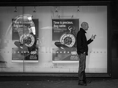 Buying Time (Leanne Boulton) Tags: life street city uk light shadow people urban blackandwhite bw white man black detail male texture monochrome face standing canon 50mm mono scotland living blackwhite natural display humanity time outdoor expression glasgow cigarette candid smoke culture streetphotography streetlife scene smoking human shade 7d posture smoker juxtaposition widow society tone facial candidstreetphotography