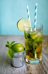 cold tea cocktail with ice and straw on board (coolnina) Tags: summer cold color green ice water glass leaf bucket tea vibrant object board mint naturallight fresh cocktail drinks twig mojito citrus lime mohito refreshing beverages straws refreshment