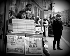 Rush hour London  - waiting for the bus on Regent Street. (alisdare1) Tags: blackandwhite monochrome holga newspapers streetphotography regentstreet busstop rushhour eveningstandard commuters pileofnewspapers fuji35mm stackofnewspapers xf35mm fujixt1