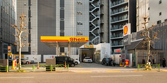 nihombashi-0492-ps-w (pw-pix) Tags: road street trees red people orange sun white black green cars yellow japan fence buildings walking grey tokyo beige shell sunny gasstation vehicles barrier petrol railing footpath fuel servicestation petrolstation tallbuildings nihombashi