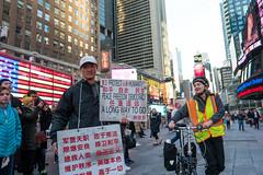 A Long Way to Go (UrbanphotoZ) Tags: plaza nyc newyorkcity woman ny newyork smile bike manhattan chinese americanflag tourists midtown timessquare zipper messenger westside levis nasdaq thelionking demonstrator alongwaytogo protecthumanityspeacefreedomdemocracy