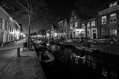 Bright Nights (McQuaide Photography) Tags: road street old city longexposure nightphotography light blackandwhite bw house holland reflection building haarlem water netherlands monochrome dutch architecture night zeiss photoshop outside boot mono licht boat canal blackwhite still lowlight europe nacht outdoor sony tripod nederland peaceful wideangle oldbuildings calm oldhouse adobe fullframe alpha huis residential oud tranquil stad manfrotto noordholland gebouw gracht lightroom huizen straat wideanglelens 1635mm northholland groothoek bakenessergracht variotessar mirrorless sonyzeiss mcquaidephotography a7rii ilce7rm2