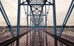 Walnut Street Bridge - Chattanooga, Tennessee (Andrea Moscato) Tags: wood city bridge blue light shadow sky usa reflection wet water rain silhouette architecture clouds america us iron downtown nuvole day view unitedstates walk perspective vivid structure ponte walkway cielo vista architettura citt legno riflesso statiuniti andreamoscato