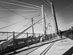 Bridge Of The People (TMimages PDX) Tags: street city bridge people urban blackandwhite monochrome buildings portland geotagged photography photo image streetphotography streetscene photograph pedestrians pacificnorthwest suspensionbridge vignette fineartphotography iphoneography tilikumcrossing