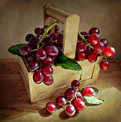 Sweet and juicy grapes. (Through Serena's Lens) Tags: life light shadow red stilllife texture leaves fruit wooden juicy still basket sweet mint grapes tabletop diamondclassphotographer flickrdiamond
