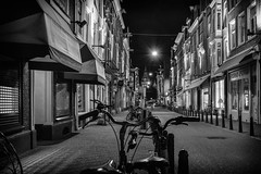 Let's Ride (McQuaide Photography) Tags: road street city longexposure nightphotography light urban blackandwhite bw holland window netherlands monochrome dutch amsterdam bike bicycle shop retail architecture night photoshop canon shopping eos mono evening licht blackwhite europe dof nacht availablelight tripod nederland streetphotography depthoffield shops winkel fullframe dslr avond depth 1740mm fietsen stad fiets manfrotto noordholland winkelstraat lightroom straat 6d lseries nieuwespiegelstraat northholland canon6d mcquaidephotography