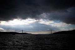 İki karanlık arasında / Surrounded by darkness yet enfolded in light (Atakan Eser) Tags: bridge light sea cloud turkey darkness gray istanbul deniz bosphorus bulut ışık karanlık i̇stanbul türkiye boğaziçi dsc90894 boğazköprüsü