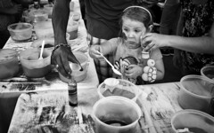 Ooops! (Anne Worner) Tags: street blackandwhite bw girl monochrome children real mono holding child sad expression candid patterns streetphotography spoon monochromatic georgetown blonde tables oops sandpainting adults ricohgr scoop funnel containers anneworner upsetclothing poppyfestival2016