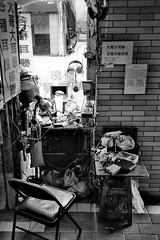 unattended roadside headphone repair shop. (howard-f) Tags: street old urban blackandwhite bw film analog 35mm taiwan streetphotography urbanexploration taipei analogue filmcamera grainy demolished analogphotography urbanplanning repairshop 台北市 北門 nikon35ti filmphotography 眷村 oldneighborhood filmisnotdead 大同區 grainyphoto abandonedneighborhood 鄭州街 塔城街 demoed 西寧北路 台鐵宿舍 臺北機器局
