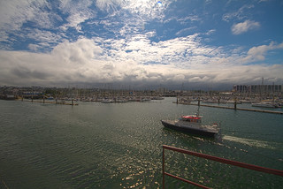 The harbour pilot's boat against a forest of yacht masts under spectacular clouds at Cherbourg, Cotentin, Normandy, France