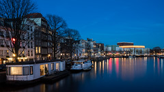 Amstel Blue (McQuaide Photography) Tags: city blue winter light urban holland reflection water netherlands dutch amsterdam skyline architecture zeiss photoshop river outside boot licht boat twilight lowlight europe waterfront outdoor dusk widescreen sony tripod capital nederland houseboat peaceful atmosphere panoramic calm illuminated adobe bluehour fullframe alpha operahouse 169 tranquil waterside stad amstel manfrotto noordholland lightroom stopera rivier capitalcity 1635mm woonboot northholland a7ii variotessar mirrorless sonyzeiss dutchnationalopera nationaleoperaballet mcquaidephotography ilce7m2